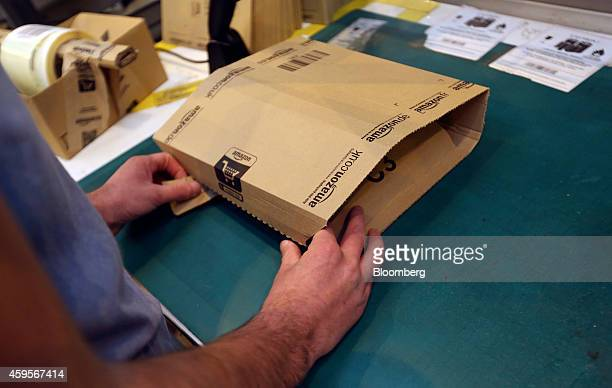 An employee seals a packaged customer order into an Amazon branded cardboard delivery box ahead of shipping at one of Amazoncom Inc's fulfillment...