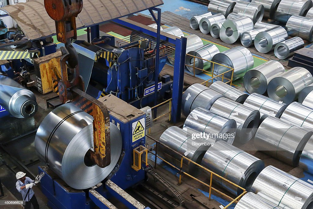 An employee secures a belt wrap to a coil of galvanized steel held by a coil grab crane at the manufacturing facility of Uttam Galva Steels Ltd the...