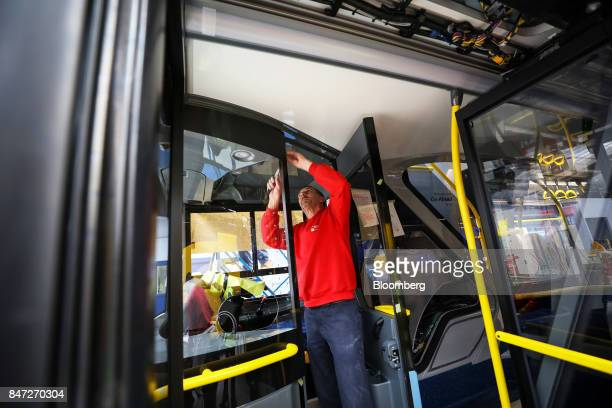 An employee secures a fitting in the drivers cab of an Enviro 400 London bus at the Alexander Dennis Ltd factory in Scarborough UK on Wednesday Sept...
