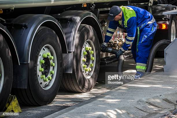 An employee secures a fuel hose to his petrol tanker as he prepares to refuel petrol pumps at a gas station operated by MOL Hungarian Oil Gas Plc in...