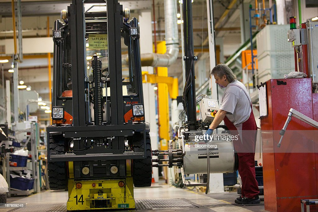 An employee secures a wheel on a Linde H25 forklift truck as its sits on the production line at the Linde Material Handling GmbH factory, a unit of Kion Group AG, in Aschaffenburg, Germany, on Tuesday, Nov. 12, 2013. Kion Group AG, the German forklift-maker which listed shares in June, is looking to expand its global sales network via acquisitions to catch up with main competitor Toyota Industries Corp. Photographer: Krisztian Bocsi/Bloomberg via Getty Images