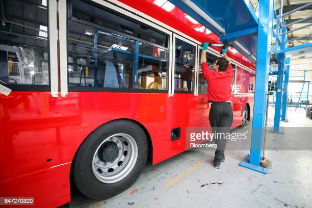 An employee secures a window into position on an Enviro 400 London bus at the Alexander Dennis Ltd factory in Scarborough UK on Wednesday Sept 13...