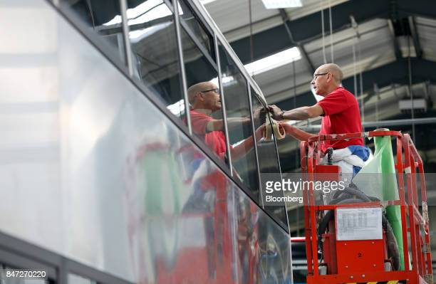 An employee secures a window on an Enviro 400 bus under construction at the Alexander Dennis Ltd factory in Scarborough UK on Wednesday Sept 13 2017...