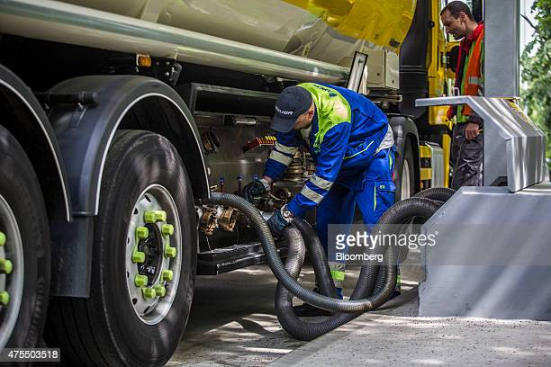 An employee secures fuel hoses from a petrol tanker as he prepares to refuel petrol pumps at a gas station operated by MOL Hungarian Oil Gas Plc in...