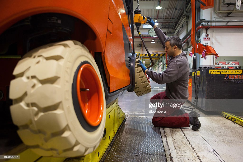 An employee secures wheels onto a Linde E25 electric forklift truck as its sits on the production line at the Linde Material Handling GmbH factory, a unit of Kion Group AG, in Aschaffenburg, Germany, on Tuesday, Nov. 12, 2013. Kion Group AG, the German forklift-maker which listed shares in June, is looking to expand its global sales network via acquisitions to catch up with main competitor Toyota Industries Corp. Photographer: Krisztian Bocsi/Bloomberg via Getty Images