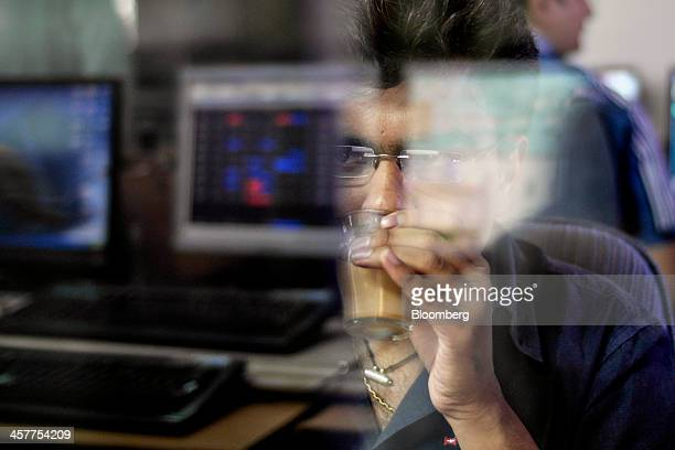 An employee seen through reflections on a glass window drinks a glass of Indian spiced chai tea as he looks at a computer monitor at a brokerage firm...