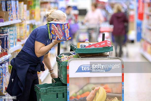 An employee selects a box of Shreddies shredded wheat cereal manufactured by Nestle SA for home delivery at the Tesco Basildon Pitsea Extra...