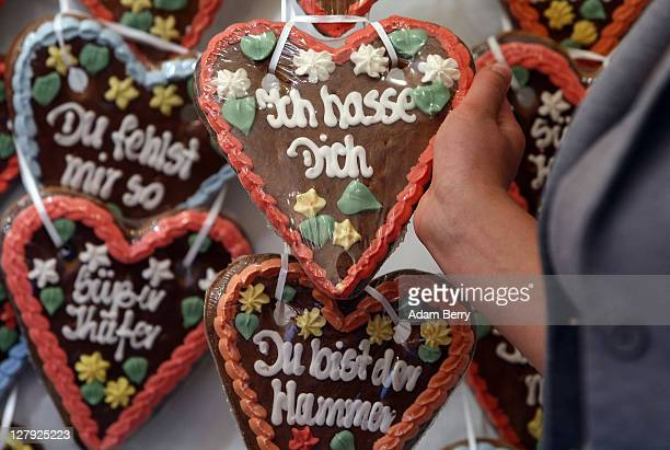 An employee selects a traditional German Lebkuchen cookie reading 'I Hate You' amongst others containing message of love during an outdoor festival...