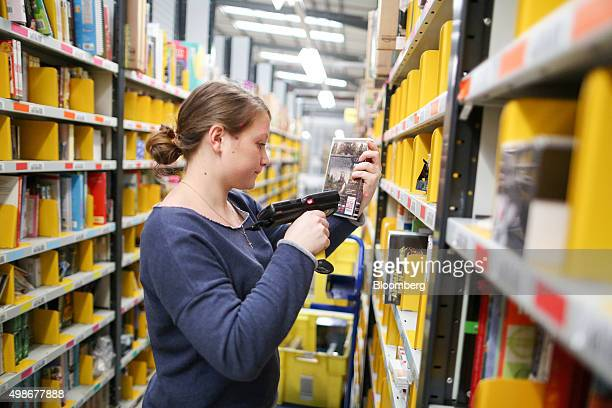 An employee selects an item for distribution at the Amazoncom Inc fulfillment center in Hemel Hempstead UK on Wednesday Nov 25 2015 WalMart and...
