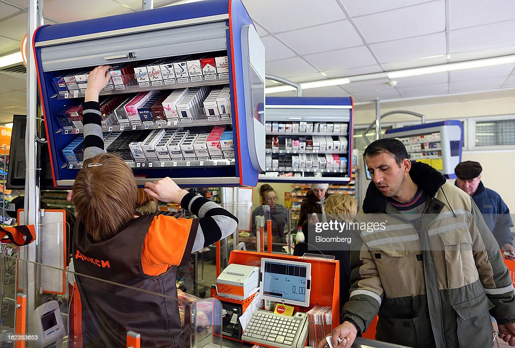 An employee selects cigarretes for a customer in the checkout desk of a supermarket operated by OAO Dixy Group in Moscow, Russia, on Friday, Feb. 22, 2013. Russia's largest retailer by market value, OAO Magnit, is spending as much as $1.8 billion this year to compete against X5 Retail Group NV and OAO Dixy Group. Photographer: Andrey Rudakov/Bloomberg via Getty Images