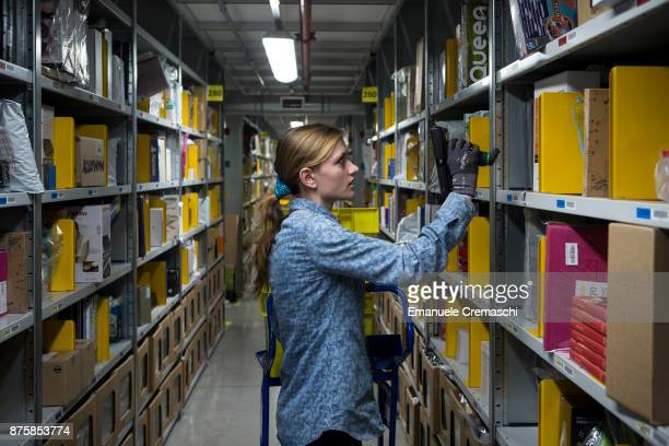 An employee selects goods from bays of merchandise as she processes customer orders at the Amazoncom MPX5 fulfillment center on November 17 2017 in...
