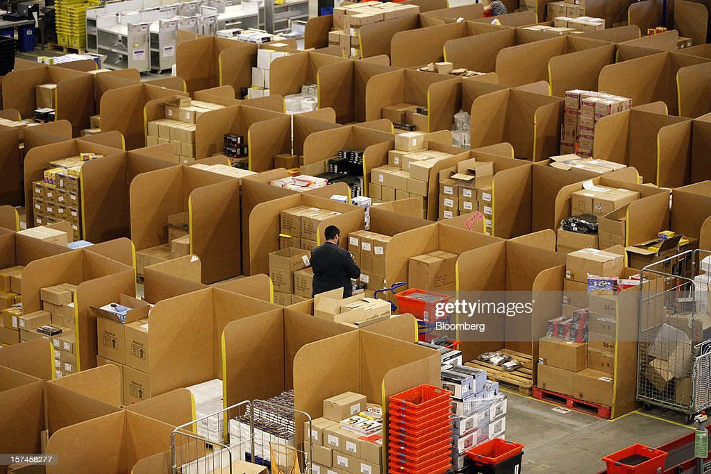 An employee selects goods from storage units ahead of packaging for delivery at the Amazon.co.uk Marston Gate 'Fulfillment Center,' the U.K. site of Amazon.com Inc. in Ridgmont, U.K., on Monday, Dec. 3, 2012. U.K. consumer confidence unexpectedly increased to an 18-month high in November as Britons become more optimistic about the economy and their finances, GfK NOP Ltd. said. Photographer: Simon Dawson/Bloomberg via Getty Images