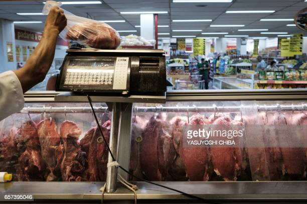 An employee sells meat during an inspection by Rio de Janeiro state's consumer protection agency PROCON at a supermarket in Rio de Janeiro Brazil on...