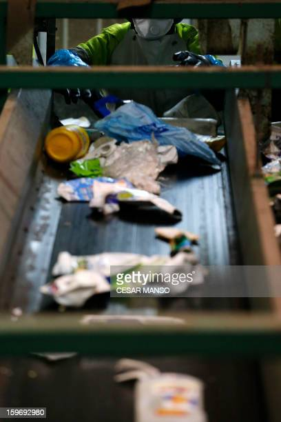 An employee separate garbage on a conveyor belt for recycling at a waste treatment plant in Burgos on January 18 2013 AFP PHOTO/ CESAR MANSO
