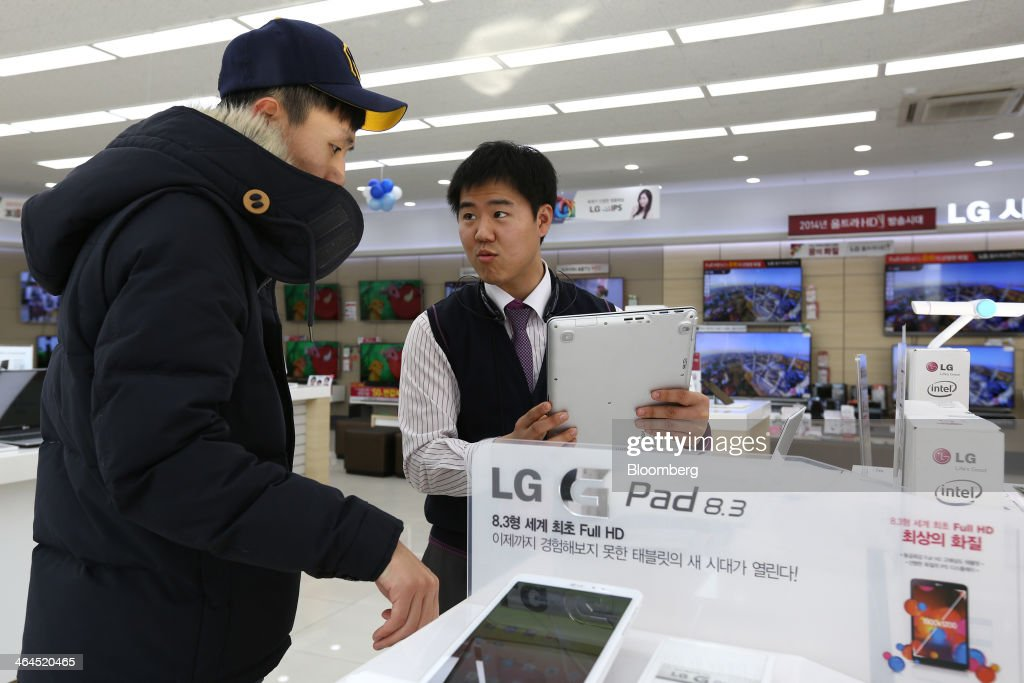 An employee serves a customer as he inspects an LG Electronics Inc. laptop computer at the company's Bestshop store in Seoul, South Korea, on Wednesday, Jan. 22, 2014. LG Electronics, the worlds second-largest seller of televisions, is scheduled to announce fourth-quarter earnings on Jan. 27. Photographer: SeongJoon Cho/Bloomberg via Getty Images