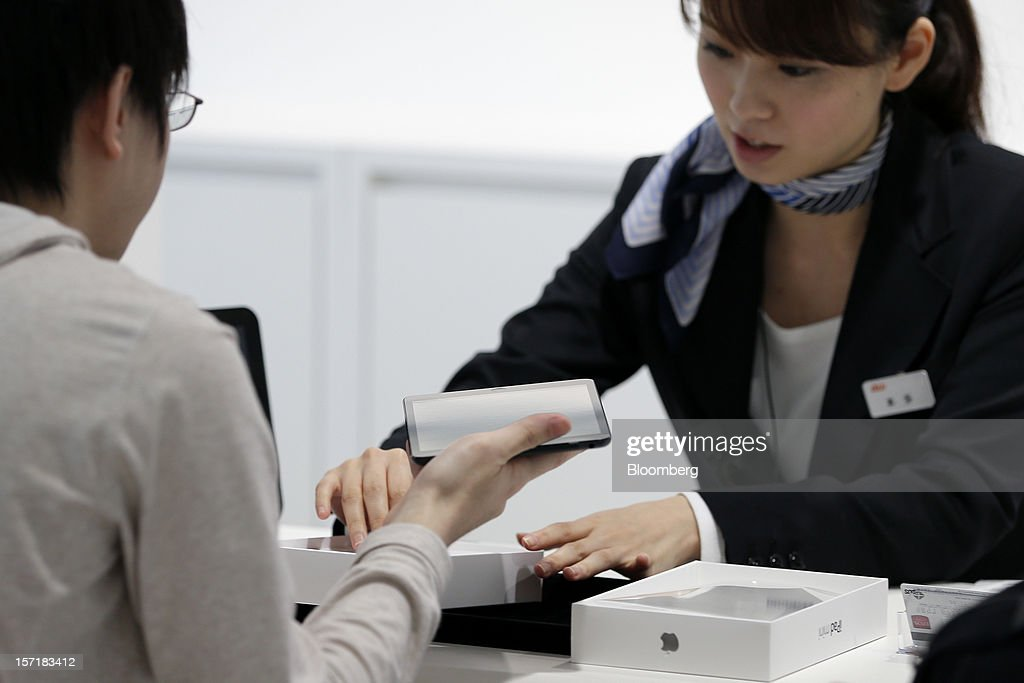 An employee serves a customer as he purchases an Apple Inc. iPad Mini at a KDDI Corp. store in Tokyo, Japan, on Friday, Nov. 30, 2012. The iPad Mini went on sale at KDDI and Softbank Corp. stores in Japan today. Photographer: Kiyoshi Ota/Bloomberg via Getty Images