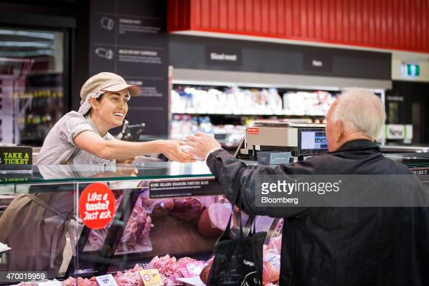An employee serves a customer at a deli counter inside a Coles supermarket operated by Wesfarmers Ltd in Sydney Australia on Tuesday Feb 18 2014...