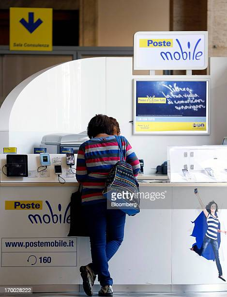 An employee serves a customer at a PosteMobile service counter inside a Poste Italiane SpA post office in Rome Italy on Wednesday June 5 2013 Rome...