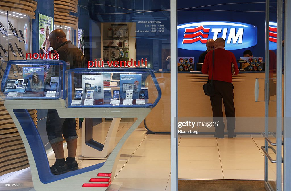 An employee serves a customer at a service desk inside a TIM store, the mobile phone unit of Telecom Italia SpA in Rome, Italy, on Monday, April 15, 2013. Telecom Italia SpA, which received approval from its board to pursue a possible merger with Hutchison Whampoa Ltd.'s Italian business 3 Italia, said billionaire Li Ka-shing's company would want control of any combined entity. Photographer Alessia Pierdomenico/Bloomberg via Getty Images
