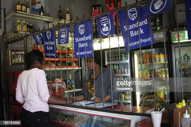 An employee serves a customer at an MPesa mobile phone money transfer point operated by Standard Bank Group Ltd at a supermarket in Tembisa near...