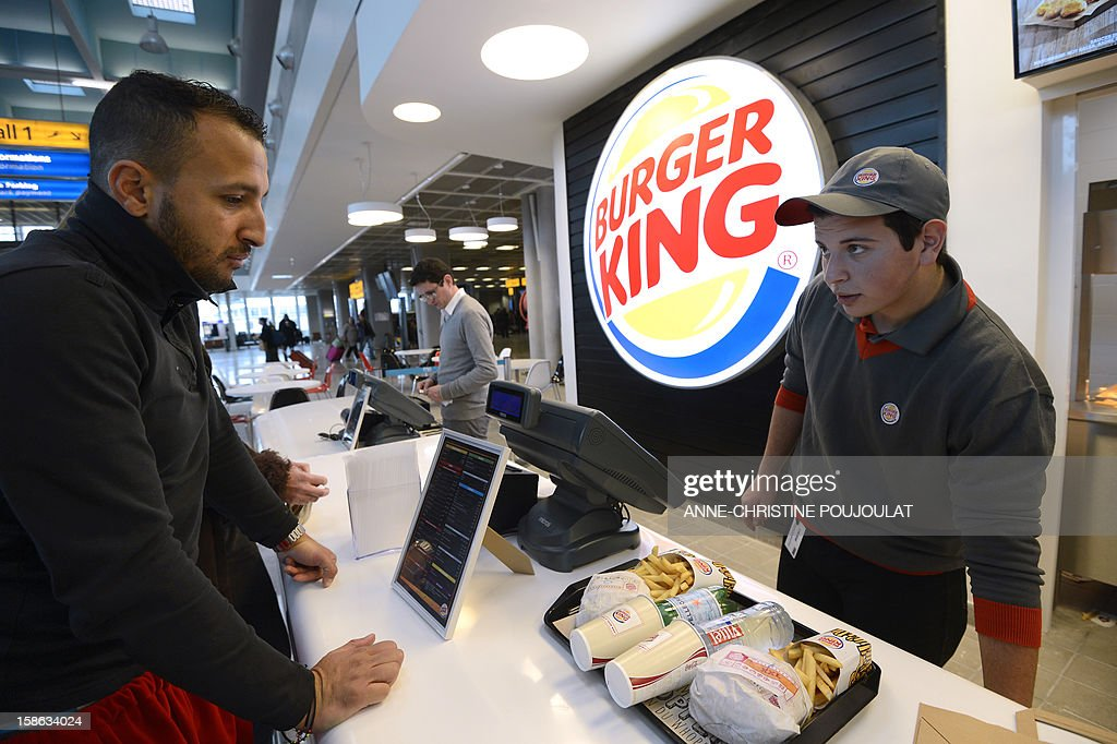 An employee (R) serves a customer at the Burger King fast food restaurant in Marseille's airport, in Marignane, southern France, on December 22, 2012. Marignane's Burger King is the first shop of the brand to open in France after 15 years of absence and marks the return of the famous Whopper burger in the country.