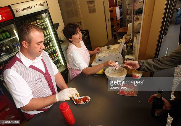 An employee serves a plate of currywurst with french fries at Konnopke's currywurst stand on July 14 2012 in Berlin Germany Currywurst originally...