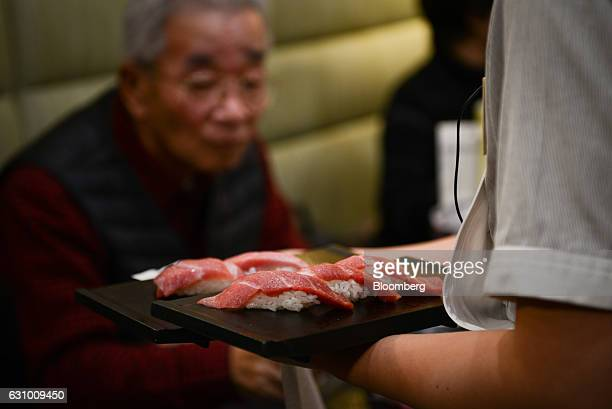 An employee serves a plate of sushi prepared from a tuna that was bought at the year's first auction at Tsukiji Market in Tokyo Japan on Thursday Jan...