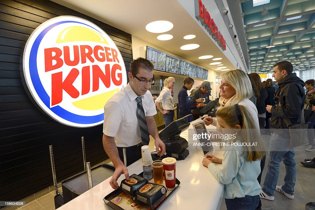 An employee (L) serves customers at the Burger King fast food restaurant in Marseille's airport, in Marignane, southern France, on December 22, 2012. Marignane's Burger King is the first shop of the brand to open in France after 15 years of absence and marks the return of the famous Whopper burger in the country.