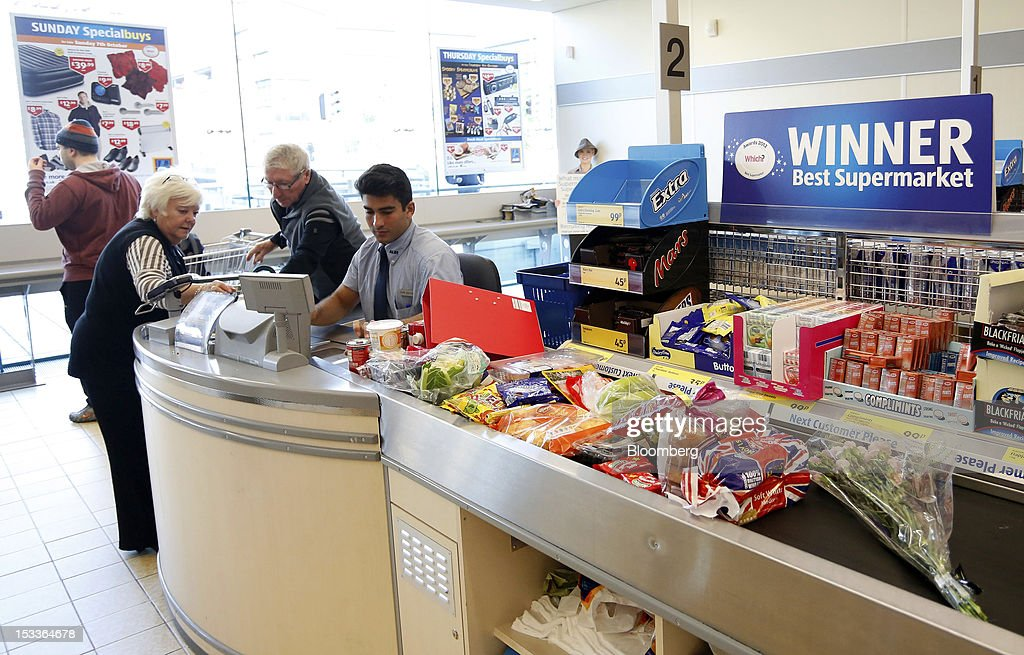 An employee serves customers at the check-out counter in a supermarket operated by Aldi Group, Germany's biggest discount-food retailer, in this arranged photograph in Manchester, U.K., on Thursday, Oct. 4, 2012. U.K. shop-price inflation slowed in September as retailers offered discounts to attract cash-strapped consumers, the British Retail Consortium said. Photographer: Paul Thomas/Bloomberg via Getty Images
