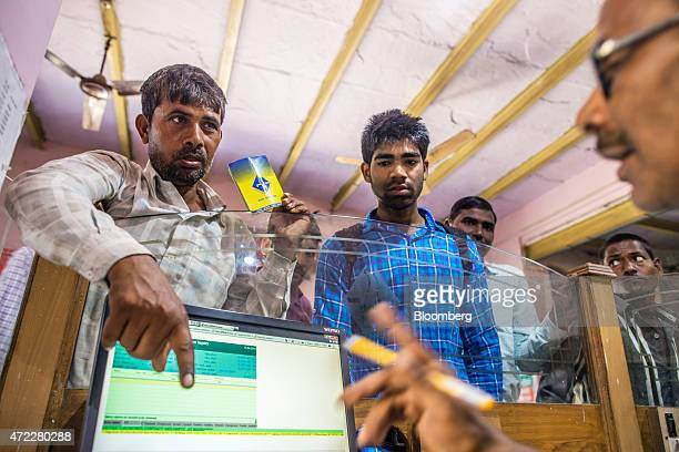 An employee serves customers inside a branch of Gramin Bank of Aryavat sponsored by Bank of India in the village of Khurana Uttar Pradesh India on...