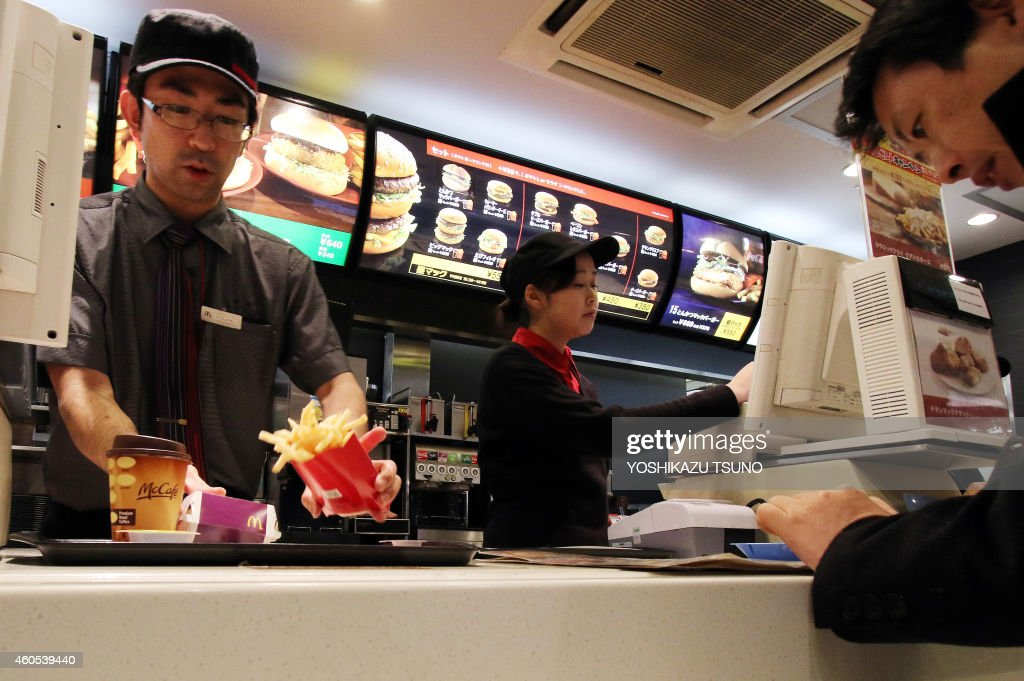 An employee serves french fries to a customer at a McDonald's restaurant in Tokyo on December 16 2014 McDonald's in Japan said on December 16 it is...
