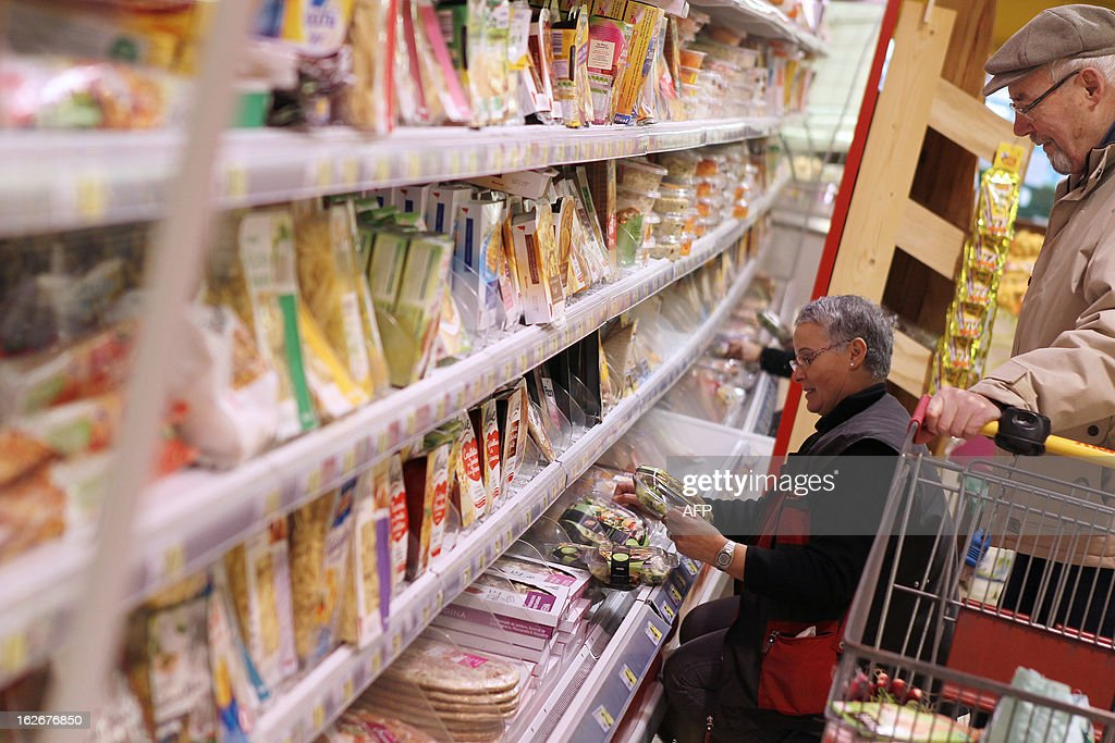 An employee sets products on a stand at a supermarket in Herouville Saint-Clair, northwestern France, on February 26, 2013.AFP PHOTO/CHARLY TRIBALLEAU.