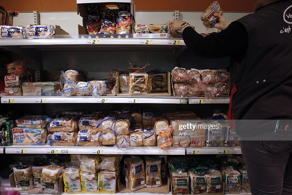 An employee sets products on a stand at a supermarket in Herouville Saint-Clair, northwestern France, on February 26, 2013. AFP PHOTO/CHARLY TRIBALLEAU.