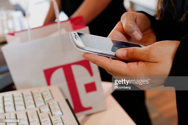 An employee sets up a new Samsung Electronics Co Galaxy 3 smartphone for a customer at a TMobile US Inc retail store in Torrance California US on...