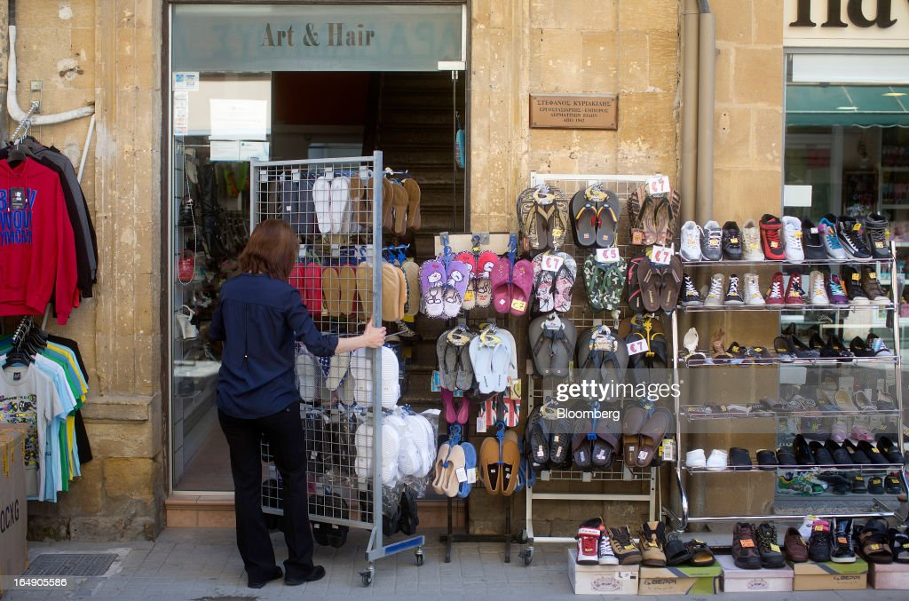 An employee sets up an outdoor display of shoes ahead of opening at a store on Ledra Street in Nicosia, Cyprus, on Friday, March 29, 2013. Cypriots face a second day of bank controls over their use of the euro as officials in Europe urged the country to move quickly to lift the restrictions, the first time they have been imposed on the common currency. Photographer: Simon Dawson/Bloomberg via Getty Images