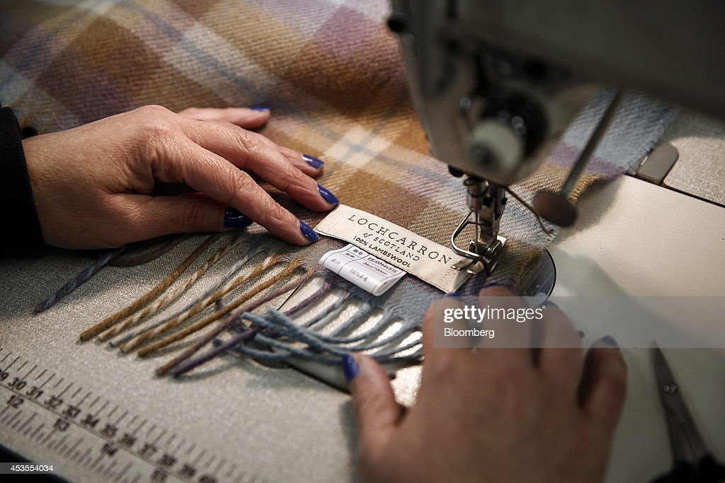An employee sews a '100% Lambswool' label onto a tartan scarf during production at Lochcarron John Buchan Ltd.'s production plant in Selkirk, U.K., on Tuesday, Aug. 12, 2014. Scottish nationalists seeking independence from the U.K. lost ground in the latest poll of voting intentions for the Sept. 18 referendum, as campaigners to keep the 307-year-old U.K. intact extended their lead. Photographer: Simon Dawson/Bloomberg via Getty Images