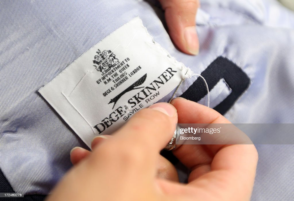 An employee sews a label into the lining of a suit jacket at the tailors Dege & Skinner based on Savile Row in London, U.K., on Tuesday, July 2, 2013. New orders at manufacturers rose for a fourth month in June, led by the textiles clothing industry, while input costs fell for a third month. Photographer: Chris Ratcliffe/Bloomberg via Getty Images