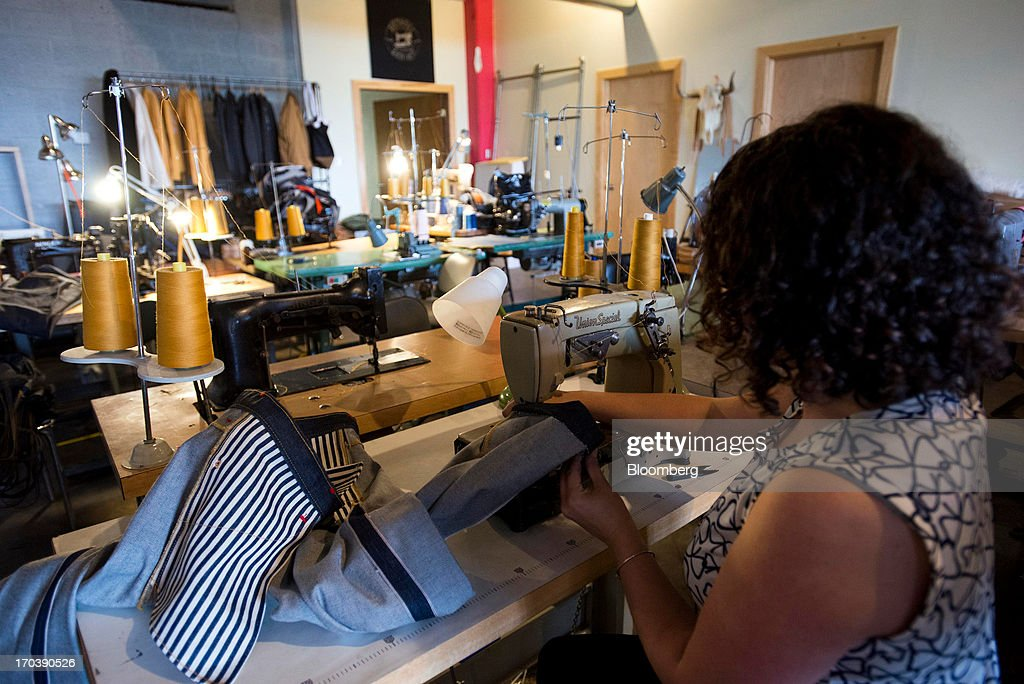An employee sews a pair of denim jeans at Detroit Denim, in Detroit, Michigan, U.S., on Wednesday, June 12, 2013. The Commerce Department is scheduled to release monthly business inventories data on June 13. Photographer: Ty Wright/Bloomberg via Getty Images