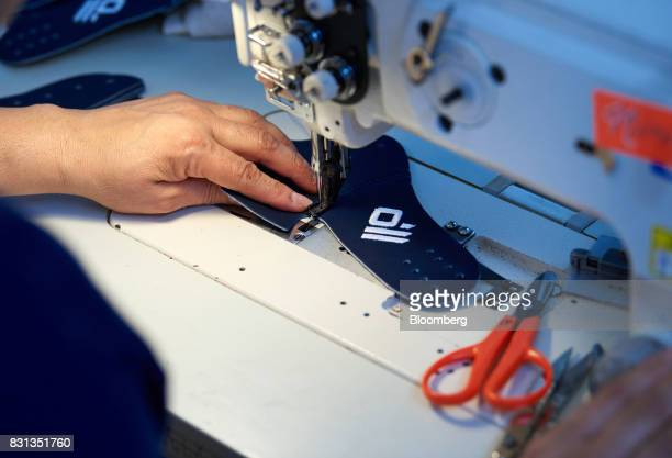 An employee sews a section of a ball glove at the Nokona manufacturing facility in Nocona Texas US on Thursday July 27 2017 Since the Great...
