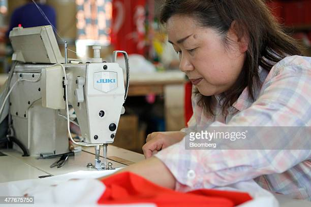 An employee sews the hem of a Japanese national flag at Tokyo Seiki Inc's manufacturing facility in Numata Gunma Prefecture Japan on Thursday June 18...