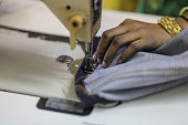 An employee sews the hem on a pair of jeans inside a jeans factory at an apparel park in the Mundargi Industrial Area of Ballari Karnataka India on...