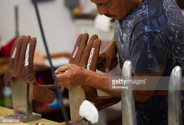 An employee shapes a ball glove on hot steel fingers at the Nokona manufacturing facility in Nocona Texas US on Thursday July 27 2017 Since the Great...