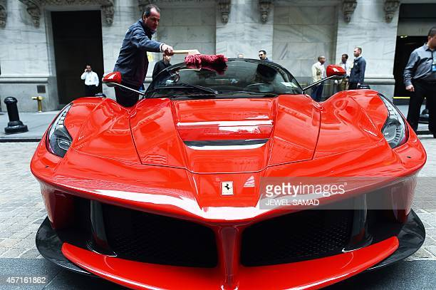 An employee shines a Ferrari LaFerrari displayed in front of the New York Stock Exchange on October 2014 in New York Italian automaker Fiat Chrysler...
