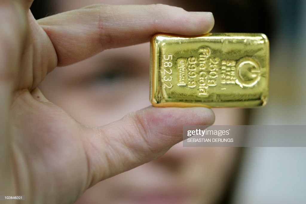 An employee shows a 250 grams gold bar on April 6 2009 at a plant of gold refiner and bar manufacturer ArgorHeraeus SA in Mendrisio southern...
