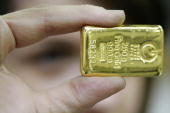 An employee shows a 250 grams golden bar on April 6 2009 at a plant of gold refiner and bar manufacturer ArgorHeraeus SA in Mendrisio southern...