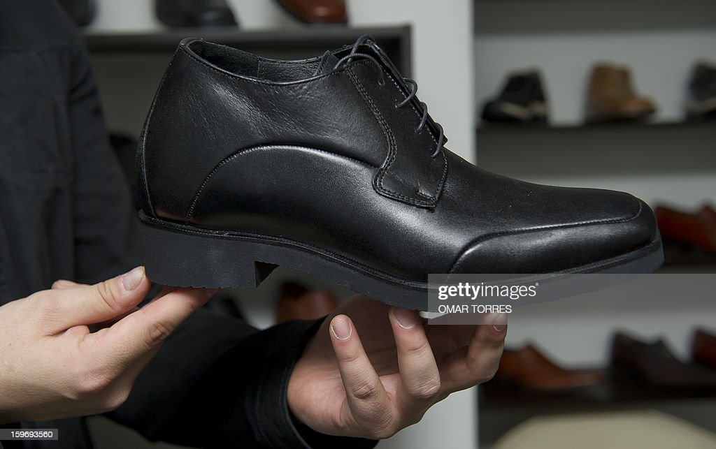 An employee shows a men shoe made with a hidden insole, to increase height, in a store in Mexico City on January 16, 2013. AFP PHOTO/ OMAR TORRES