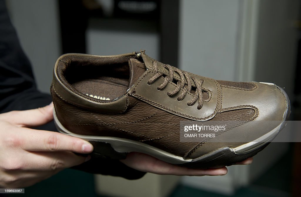 An employee shows a men shoe made with a hidden insole, to increase height, in a store in Mexico City on January 16, 2013.