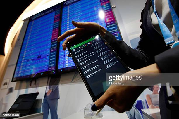 An employee shows a mobile device used in the airline industry displayed at the Samsung Innovation Museum operated by Samsung Electronics Co in Suwon...