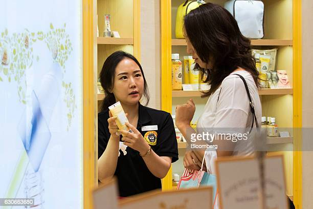 An employee shows a product information panel to a customer at a Burt's Bees Inc store a subsidiary of Clorax Co in Seoul South Korea on Thursday...