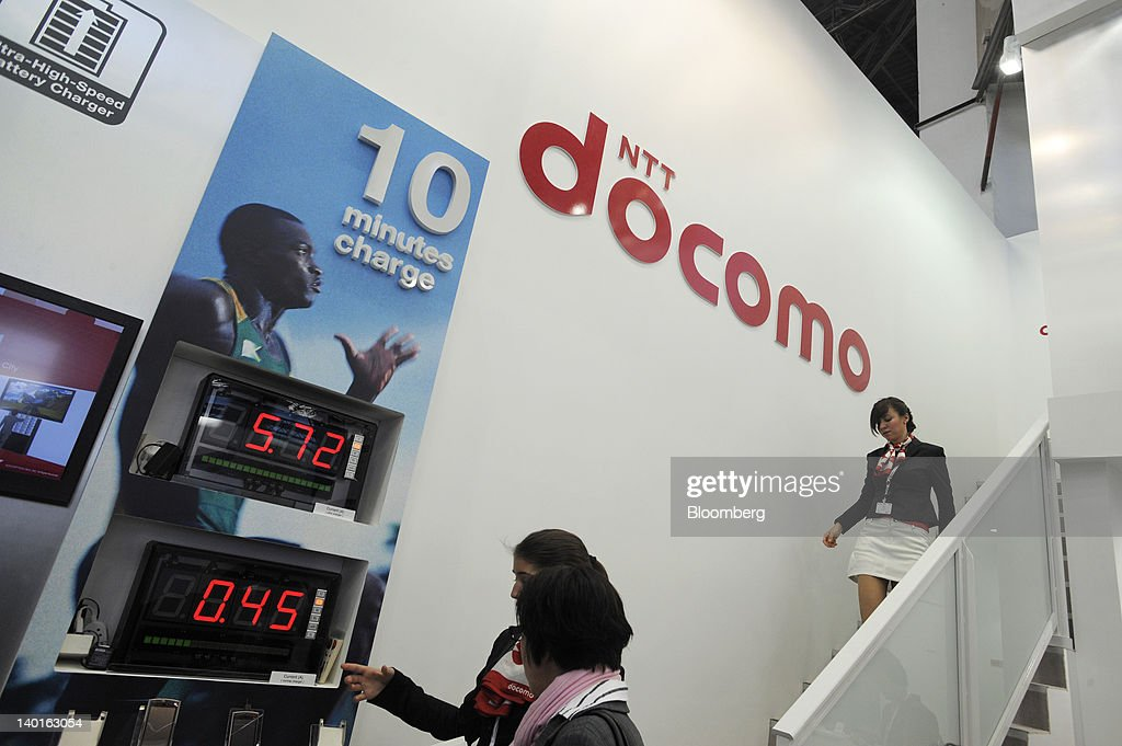 An employee shows a visitor a display of digital clocks showing the charging time for the NTT DoCoMo Inc. Medias range of smartphones at the company's booth at the Mobile World Congress in Barcelona, Spain, on Wednesday, Feb. 29, 2012. The Mobile World Congress, operated by the GSMA, expects 60,000 visitors and 1400 companies to attend the four-day technology industry event which runs Feb. 27 through March 1. Photographer: Denis Doyle/Bloomberg via Getty Images